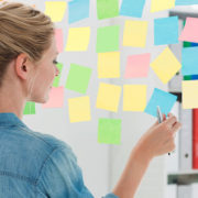 Rear view of a female artist looking at colorful sticky notes at the office